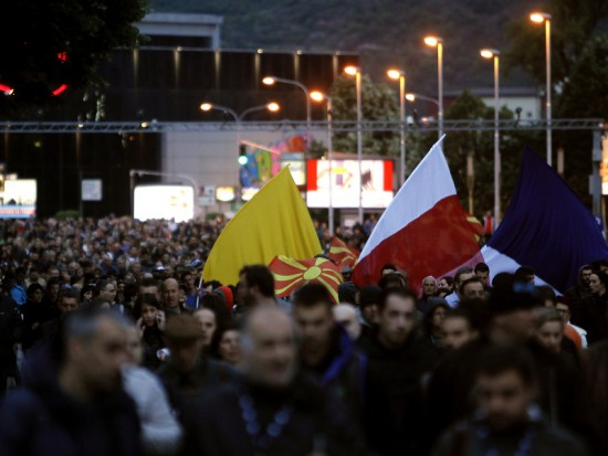 People participate in an anti-government protest, marching through Skopje, Macedonia, Tuesday, May 3, 2016. A few thousand people marched peacefully late Tuesday in Skopje, continuing the protests after the country's president pardoned dozens of politicians who were facing criminal proceedings for alleged involvement in a wiretapping scandal. (AP Photo/Boris Grdanoski)