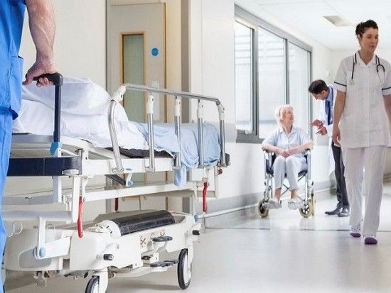 Male nurse pushing stretcher gurney bed in hospital corridor with doctors & senior female patient