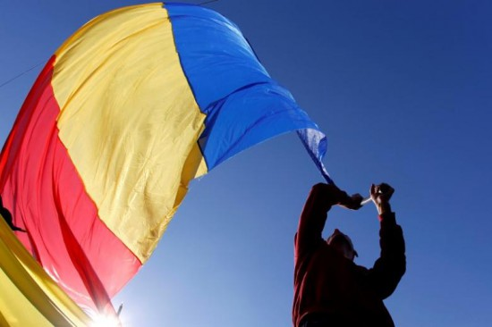 A man waves a Romanian national flag during a march in downtown Bucharest, Romania, October 20, 2013. REUTERS/Bogdan Cristel/File Photo